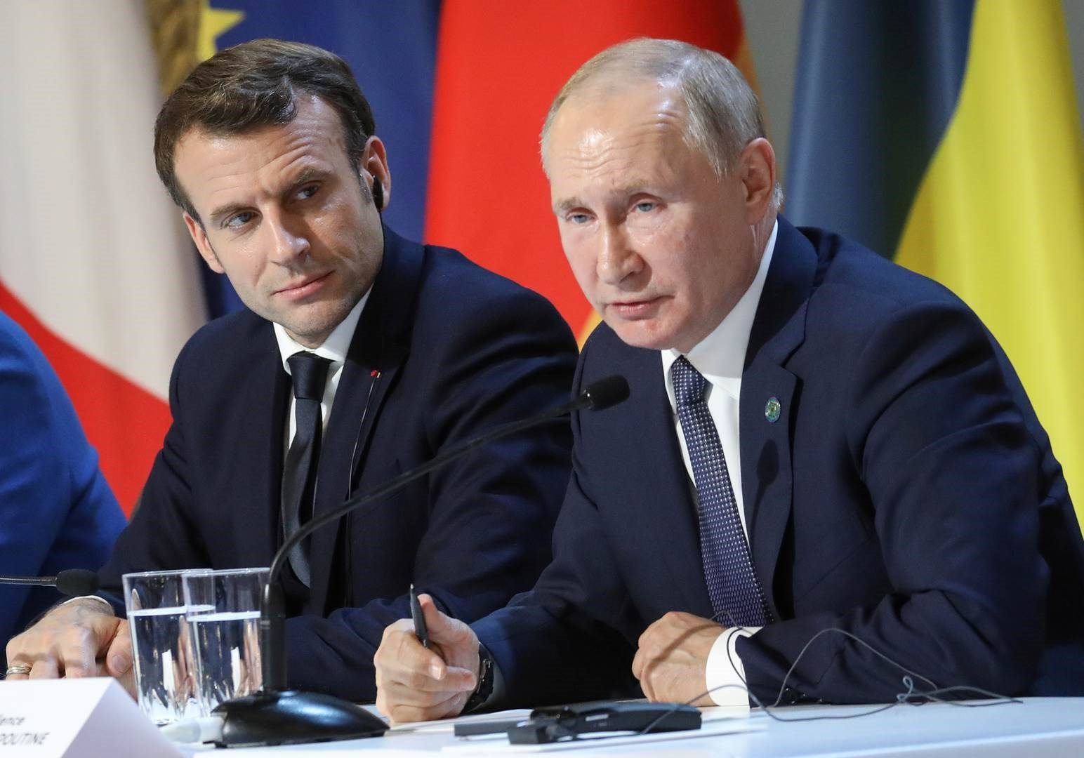 الرئيس الروسي فلاديمير بوتين يجلس بجانب نظيره الفرنسي إيمانويل ماكرون (أرشيف)