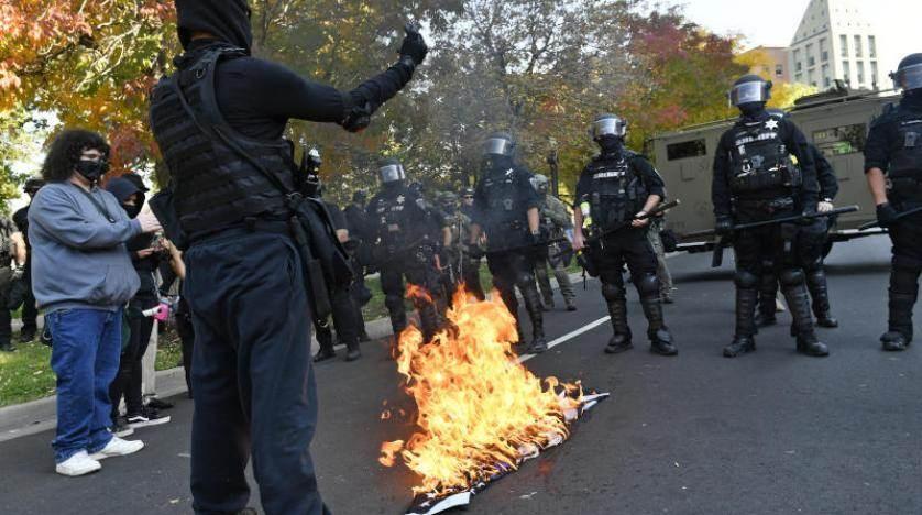 متظاهرون يحرقون علماً أمام الشرطة خلال مسيرات احتجاجية في دنفر (أ ف ب)