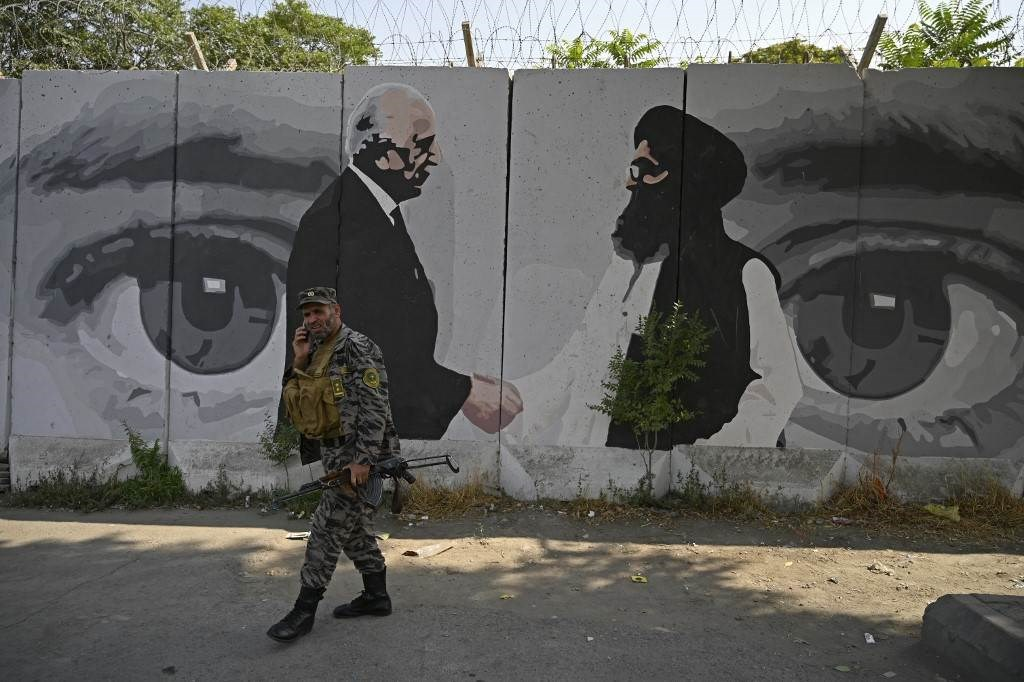 لوحة للممثل الأميركي الخاص للمصالحة في أفغانستان والملا عبد الغني بارادار في كابل (أ ف ب).