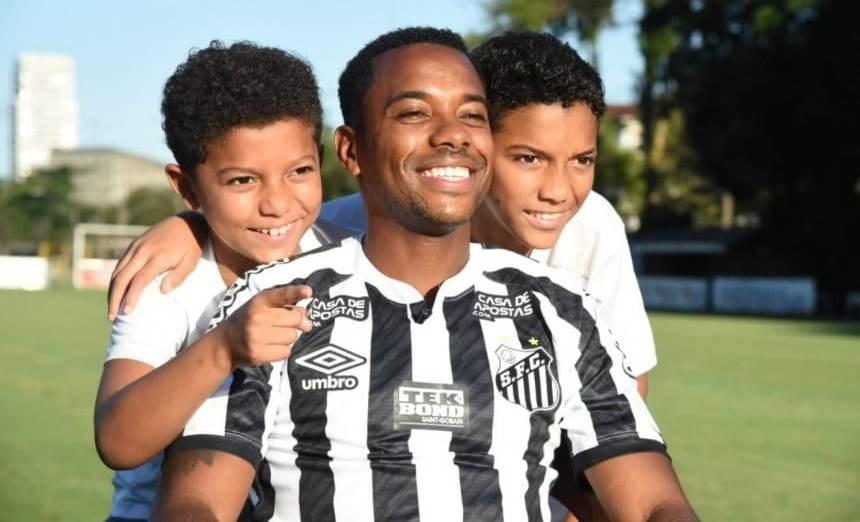 روبينيو مع ولدَيه خلال تقديمه لاعباً لسانتوس