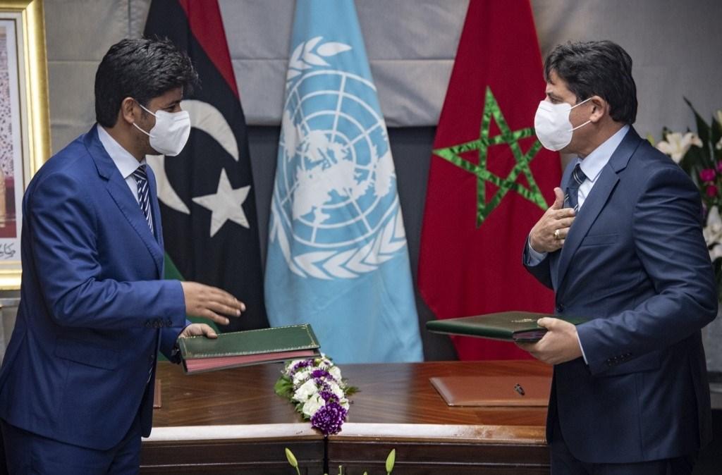 ممثلا الخصمين الليبيين يتبادلان الوثائق بعد اجتماع في مدينة تمارة الساحلية المغربية - 6 أكتوبر 2020 (أ.ف.ب)