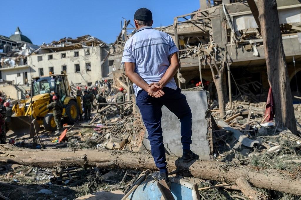 رجل يراقب رجال الإنقاذ وهم يبحثون عن ناجين في موقع انفجار في ناغورنو كاراباخ خلال الاشتباكات - 11 أكتوبر 2020 (أ.ف.ب)