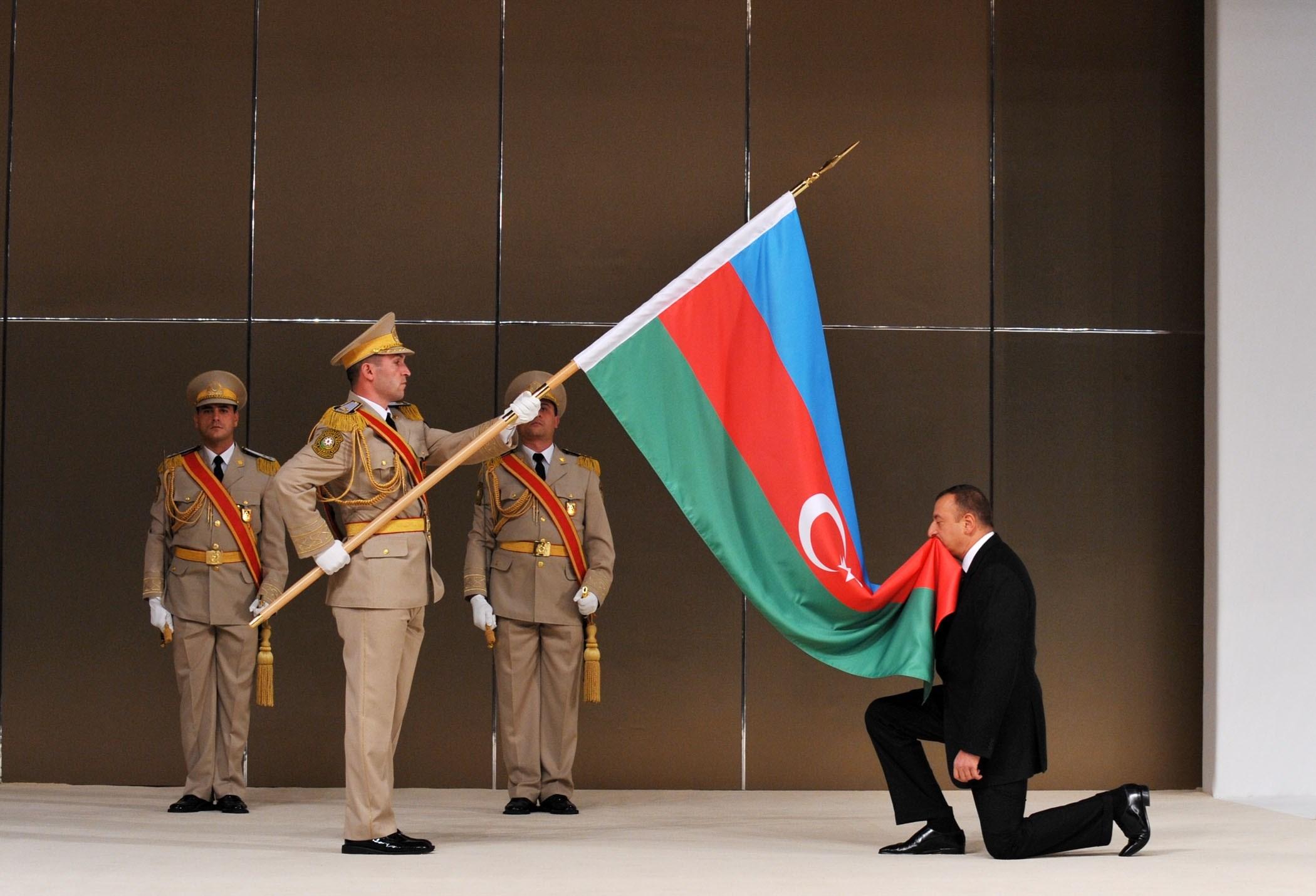 الرئيس الآذربيجاني إلهام علييف ينحني أمام علم بلاده (أرشيف)