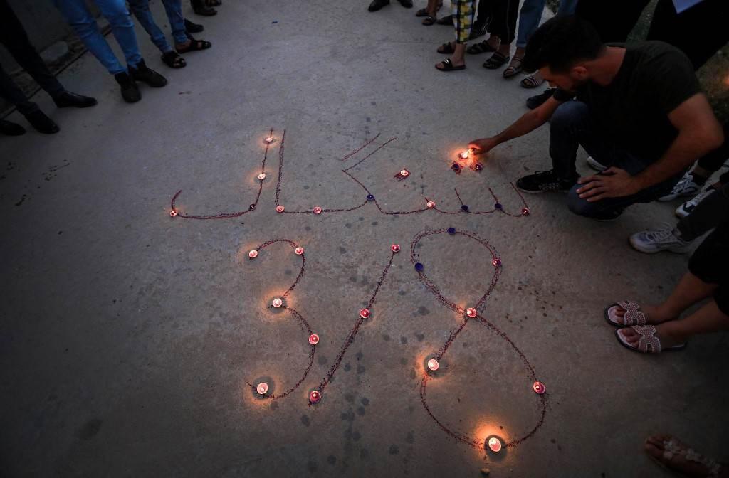 يزيديون عراقيون يضعون الشموع خلال وقفة احتجاجية في منطقة الشريعة (أ ف ب).