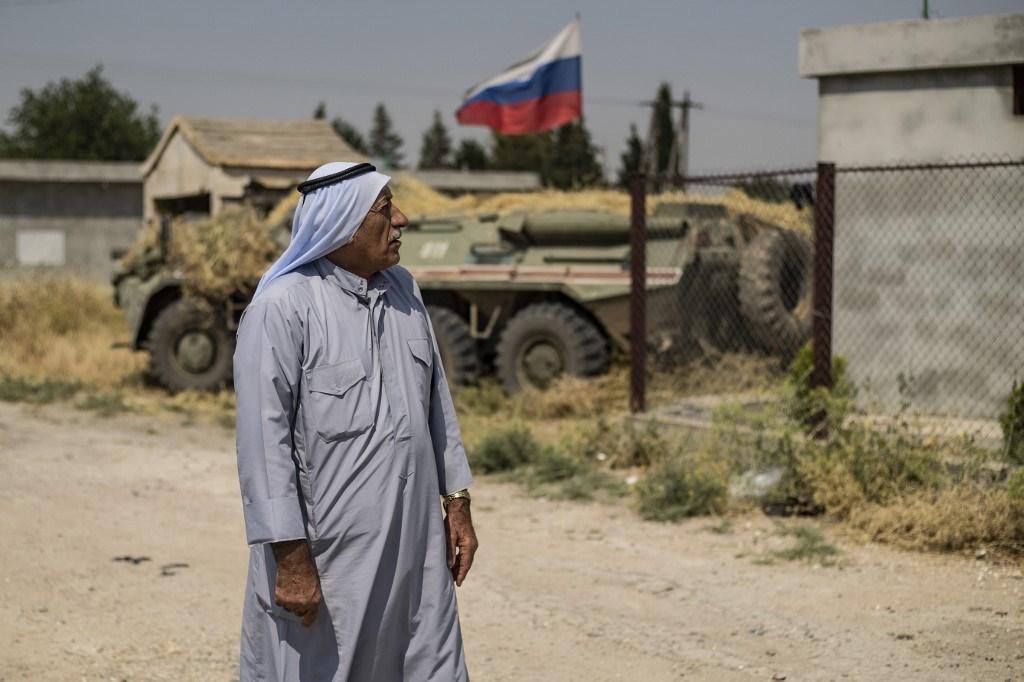 رجل مسن يمر من أمام آلية عسكرية روسية في بلدة ديرونة أرحا في سوريا (أ ف ب).
