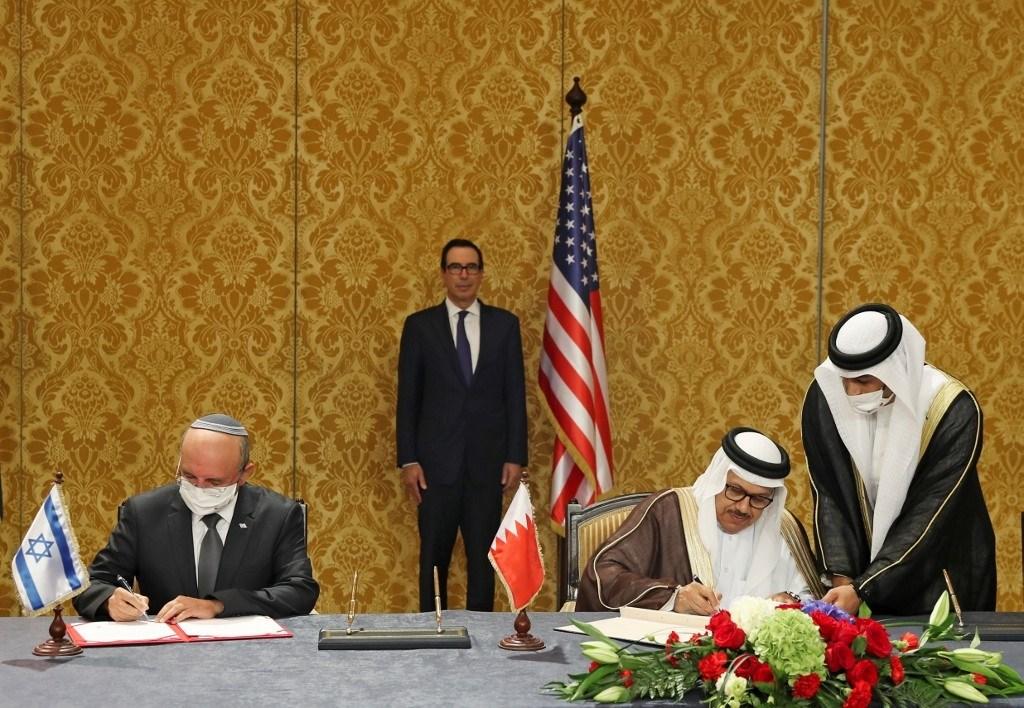 منوشين في الوسط يحضر حفل توقيع البيان المشترك بين شبات (إلى اليسار) والزياني في المنامة (أ ف ب)