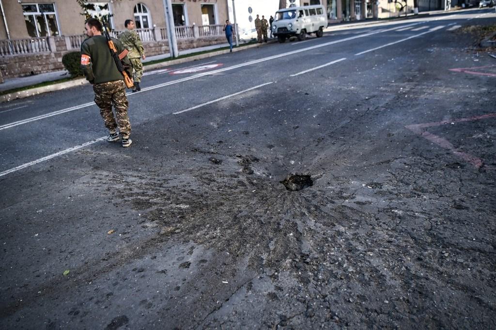 حفرة على طريق أحدثته قذائف ليلية في ستيباناكيرت أثناء القتال في ناغورنو كاراباخ (أ ف ب).