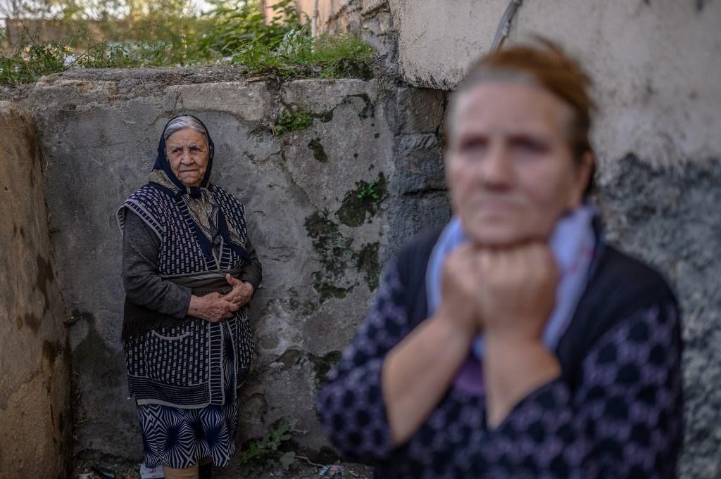 نساء يقفن عند مدخل قبو خلال قصف على مدينة ترتر، في 13 أكتوبر 2020 (أ ف ب).