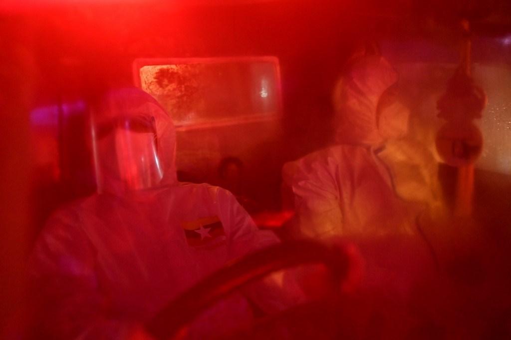 متطوعون داخل سيارة إسعاف حيث يتم نقل المشتبه بإصابتهم بكورونا في يانغون (أ ف ب).