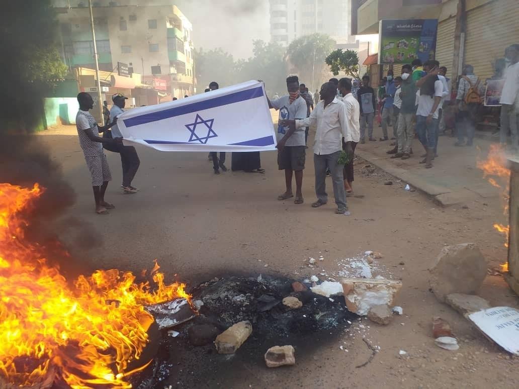 متظاهرون سودانيون يحرقون العلم الإسرائيلي احتجاجاً على اتفاق التطبيع (وسائل التواصل الاجتماعي).