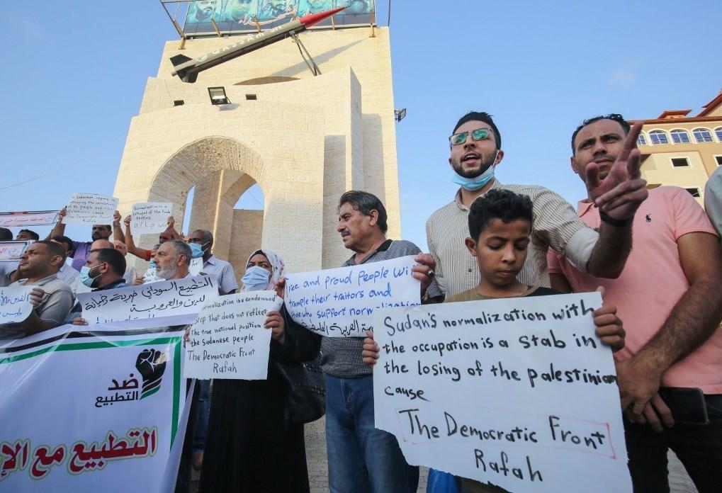 متظاهرون فلسطينيون يرفعون لافتات احتجاجا على اتفاق تطبيع السودان مع