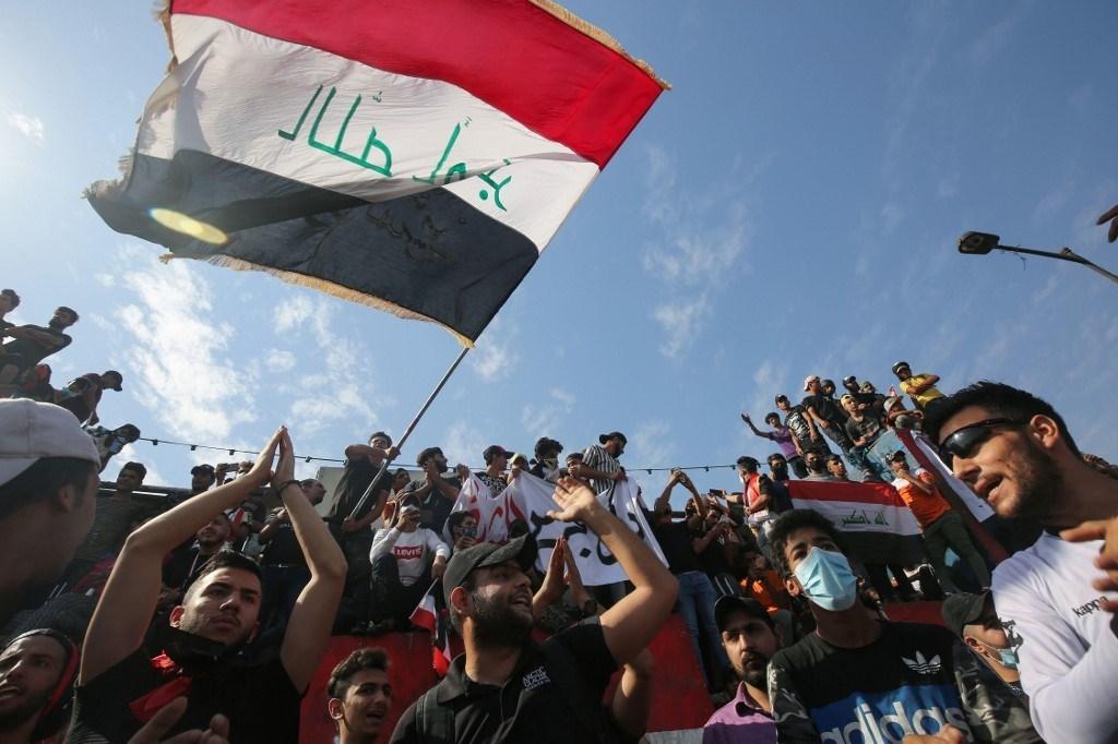 متظاهرون عراقيون يتجمعون على جسر الجمهورية بالعاصمة بغداد (أ ف ب)