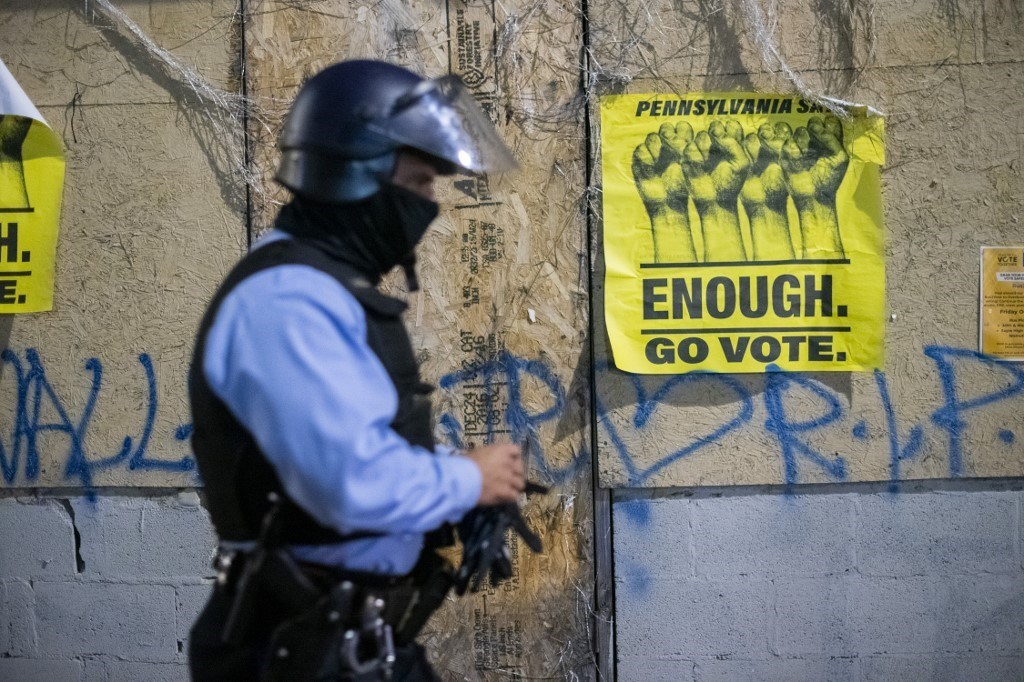شرطي أمام لافتة كتب عليها