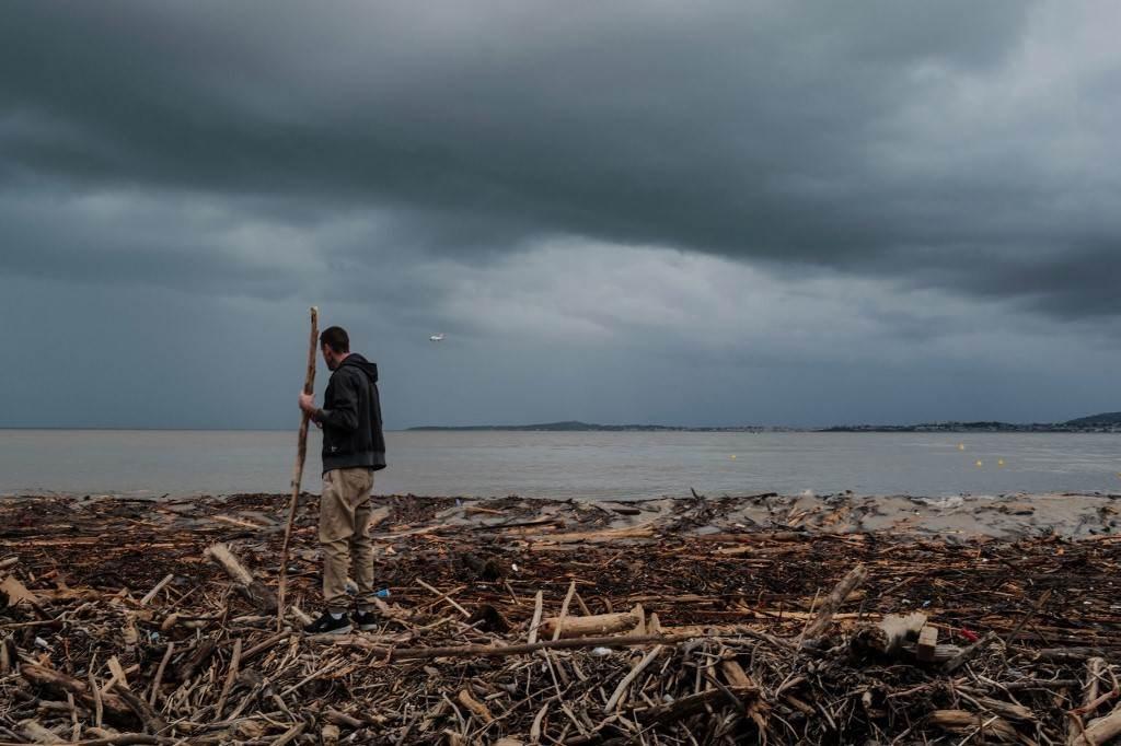 رجل يمشي على أغصان الأشجار المحطمة بعد فيضانات العاصفة