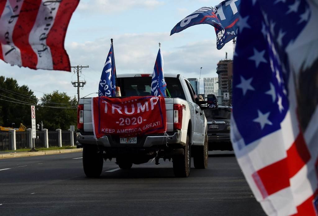 أنصار الرئيس الأميركي يقودون سياراتهم خارج مركز والتر ريد الطبي بولاية ماريلاند (أ ف ب).