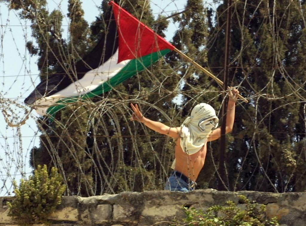 شاب يحمل العلم الفلسطيني ويرفع علامة النصر قرب المسجد الأقصى خلال اشتباكات مع الاحتلال عام 2001 (أ.ف.ب)