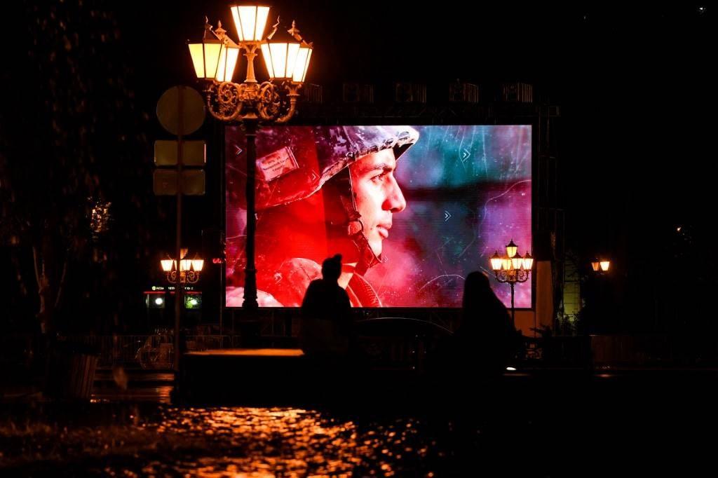 أشخاص يمشون أمام شاشة كبيرة تعرض مقاطع فيديو عسكرية وطنية في يريفان (أ ف ب).
