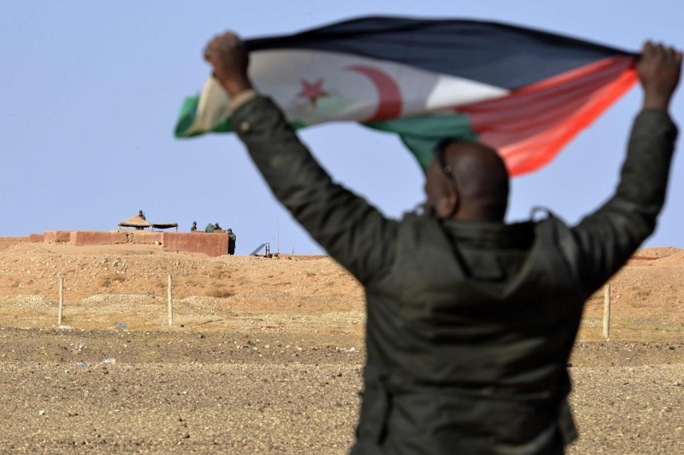 رجل صحراوي يرفع علم جبهة البوليساريو في منطقة المحبس بالقرب من جنود مغاربة يحرسون الجدار الفاصل بين الصحراء الغربية والمغرب (أ ف ب)