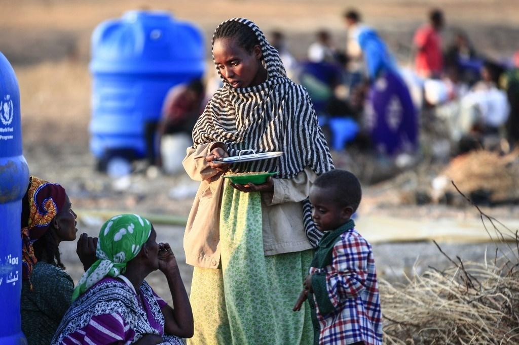 مهاجرون فروا من القتال في تيغري يجلسون في مدينة حمدية شرق السودان (أ ف ب).