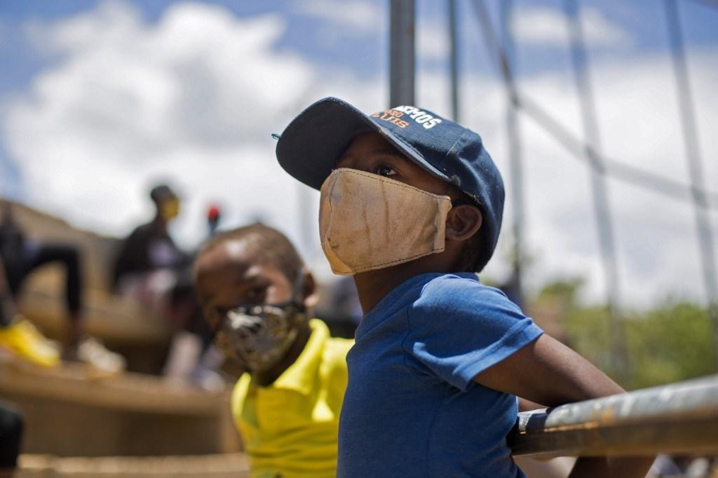 أطفال يرتدون أقنعة واقية خلال مشاهدتهم مباراة بيسبول في الدومينيكان - في 22 يوليو 2020 (أ.ف.ب)