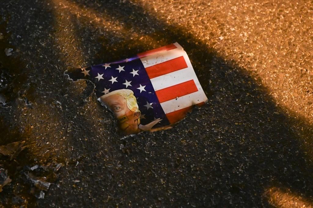 العلم الأميركي مرسوم عليه وجه ترامب محروقاً في الشارع خلال مظاهرة ضده في واشنطن - 14 نوفمبر 2020 (أ.ف.ب)