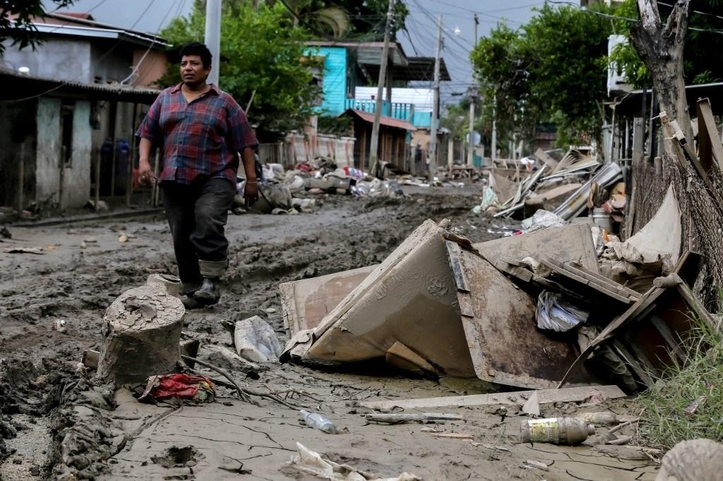 رجل يسير على طول شارع متضرر بعد مرور إعصار