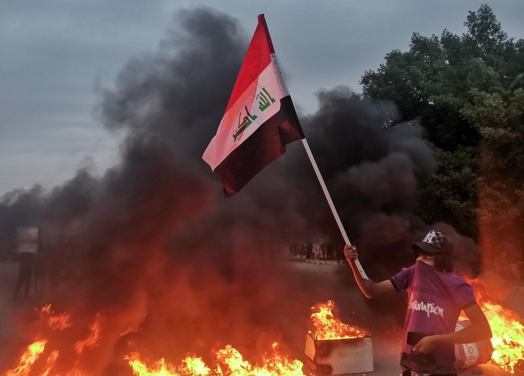 متظاهر يرفع العلم العراقي خلال إحراق الإطارات وسط اشتباكات بين متظاهرين وأنصار الصدر في الناصرية - 27 نوفمبر 2020 (أ.ف.ب)