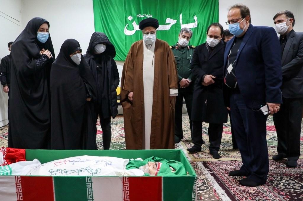 رئيسي إلى جانب عائلة الشهيد فخري زادة أثناء توديع جثمانه في طهران