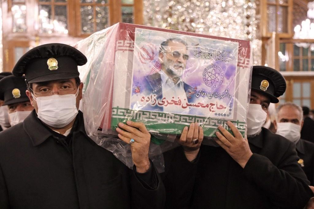 خدّام مرقد الإمام الرضا يحملون نعش العالم محسن فخري زاده في مشهد (أ ف ب).