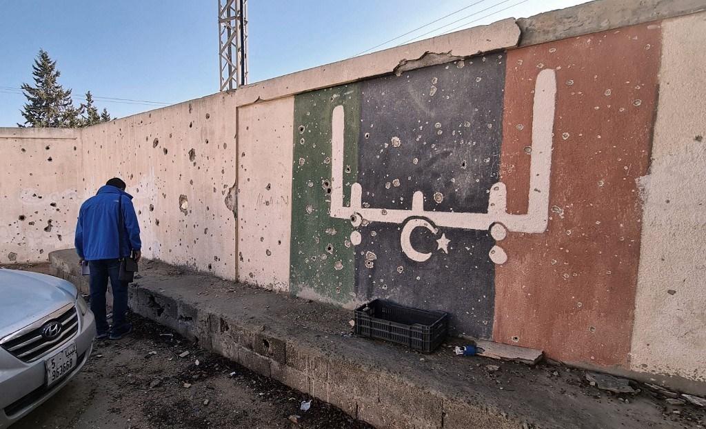 محاولة ترميم مدرسة الشهداء الليبية التي تضررت أثناء القتال بين الفصائل (أ ف ب).