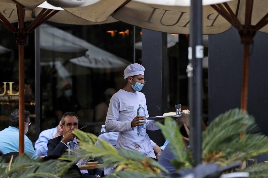 نادل يرتدي قناعاً للوقاية من فيروس كورونا في احدى مقاهي بيروت (أ ف ب).