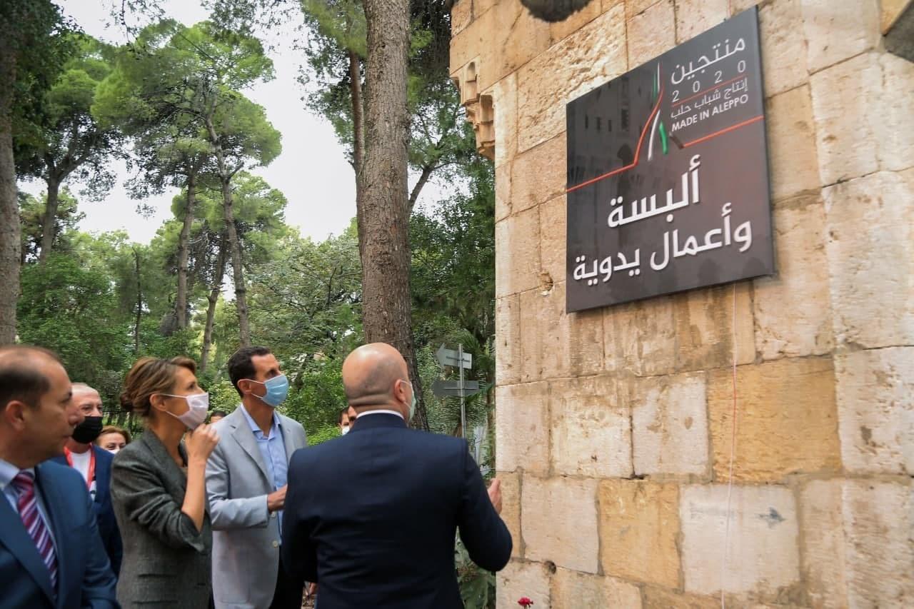 الأسد وزوجته خلال زيارته معرض
