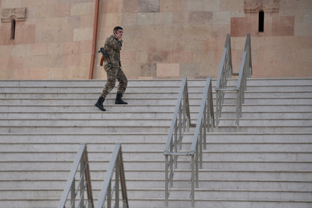 جندي احتياطي يصعد درج كاتدرائية خلال الصراع العسكري المستمر بين أرمينيا وأذربيجان (أ ف ب).