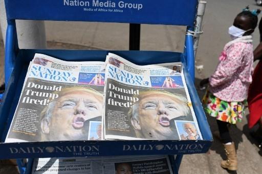 فتاة صغيرة تمر أمام صحيفة يومية كينية تحمل عنوان