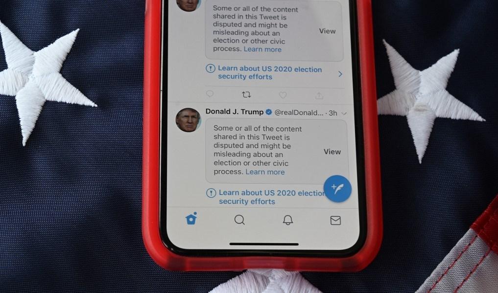 هاتف جوال يظهر عليه تغريدات للرئيس الأميركي دونالد ترامب مع وضع علامة تحذير عليها من قبل