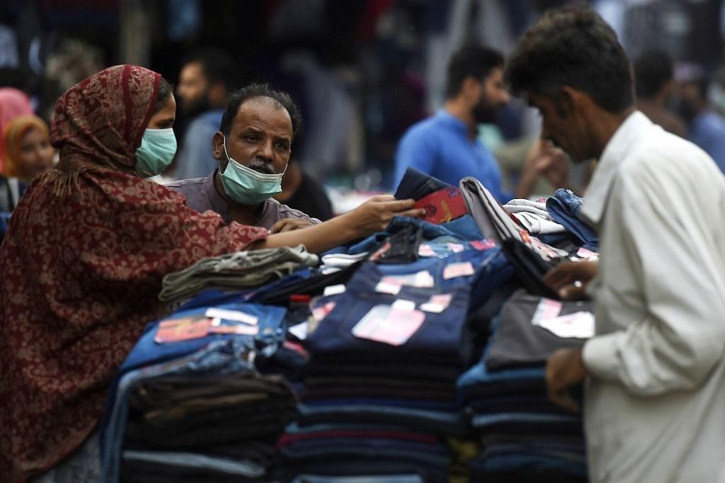 أشخاص يرتدون أقنعة للوقاية من فيروس كورونا ويشترون الملابس من سوق في كراتشي (أ ف ب).