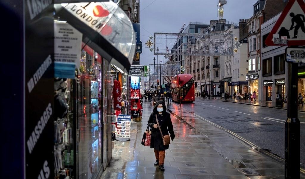 امرأة تمشي في شارع أكسفورد في لندن في اليوم الأول من قيود المستوى الثالث.