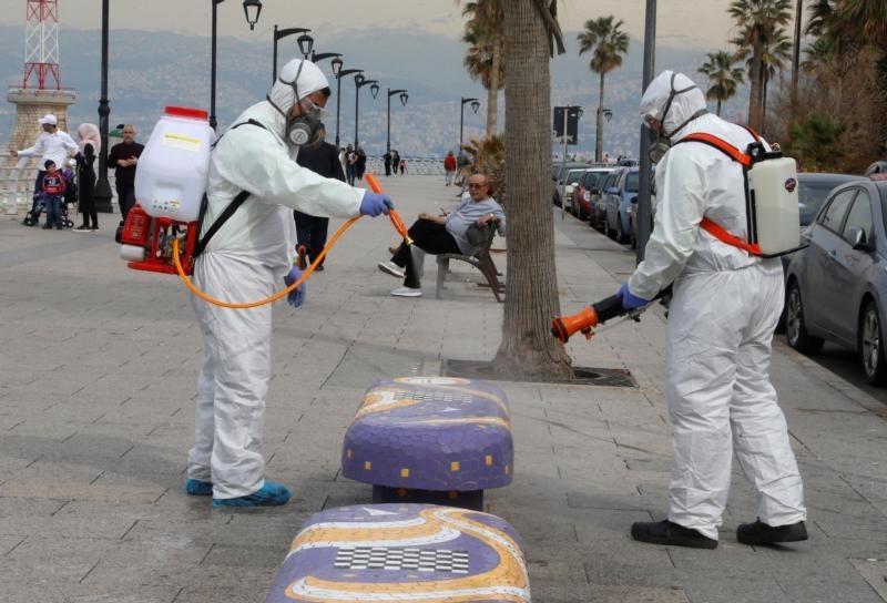 موظفون يعقمون منضدة كإجراء احترازي من انتشار فيروس كورونا في بيروت.