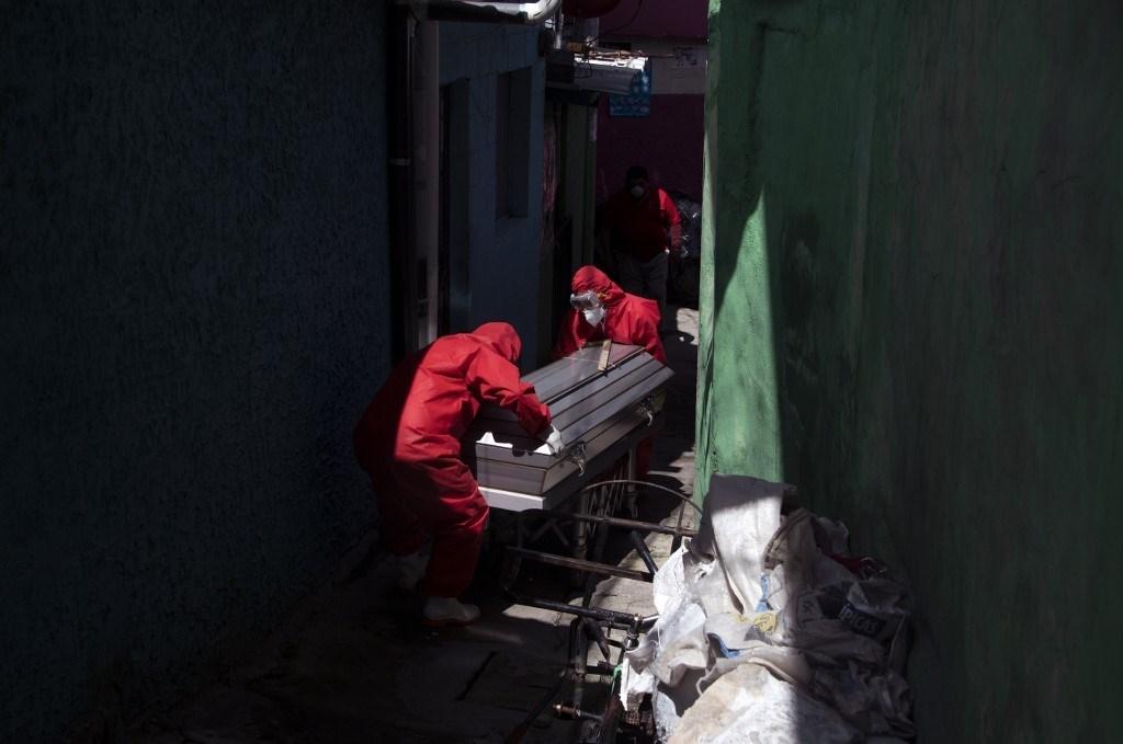 عمّال يرتدون بدلات السلامة البيولوجية يحملون جثة رجل توفي جرّاء إصابته بفيروس كورونا (أ ف ب).