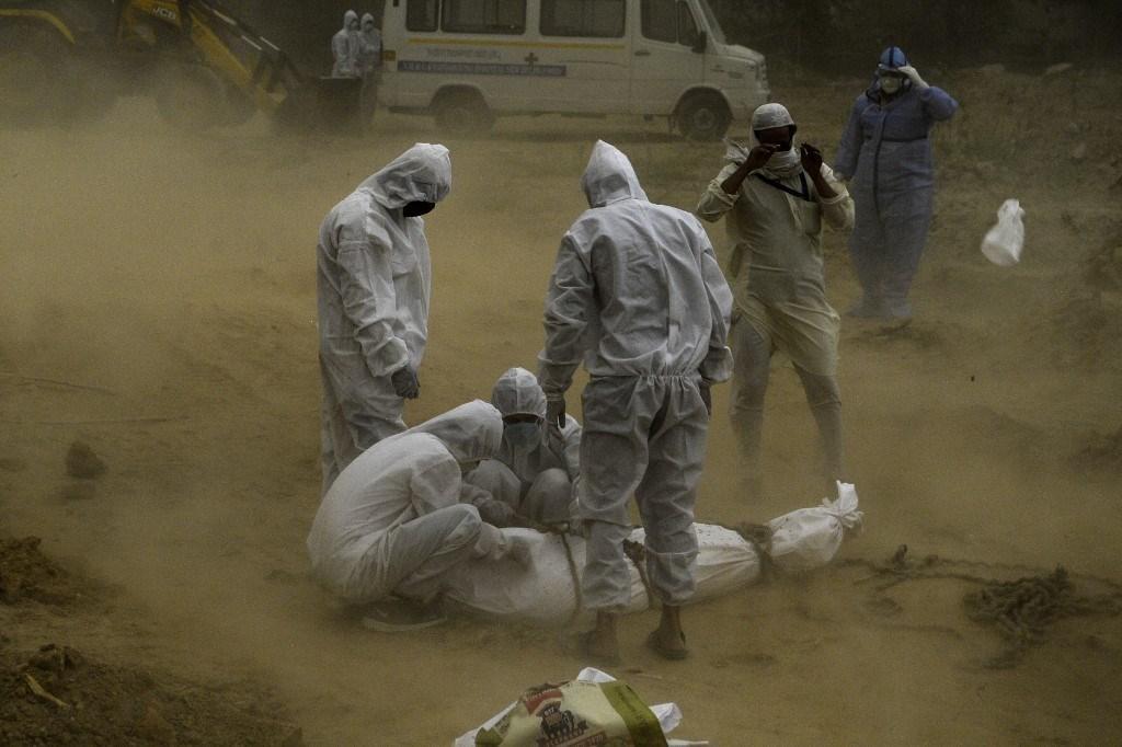 أقارب يرتدون ملابس واقية يربطون جثة ضحية ماتت بسبب فيروس كورونا في نيودلهي  (أ ف ب).