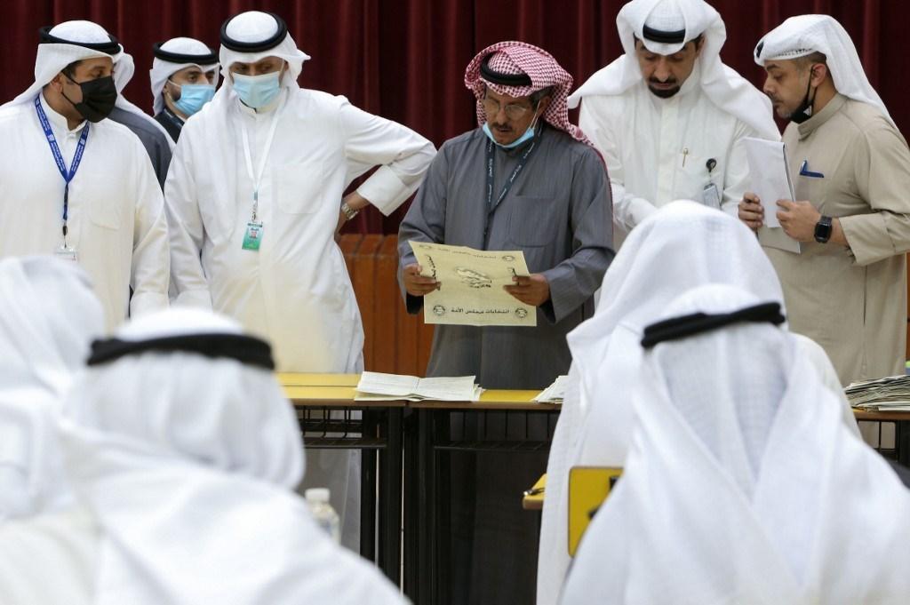 قاض كويتي ومعاونيه يقومون بفرز الأصوات في مركز اقتراع بمدينة الكويت (أ ف ب).