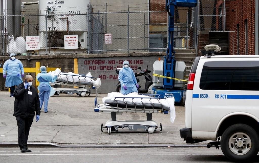عمال طبيون ينقلون جثث متوفين بمرض كورونا في نيويورك.