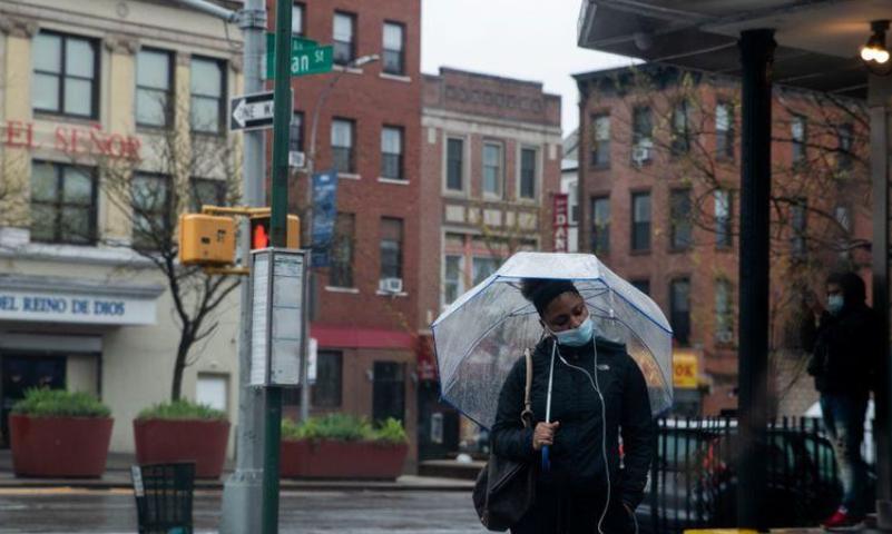 امرأة تضع كمامة تمسك بمظلة في بروكلين / نيويورك يوم الأحد (رويترز).