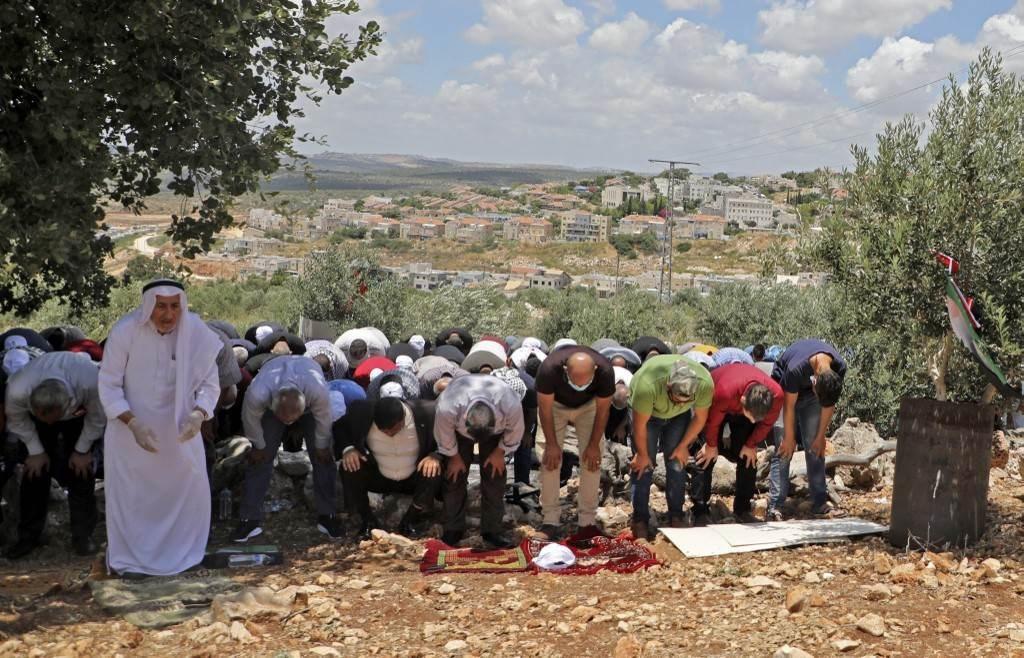 فلسطينيون يقيمون الصلاة خلال احتجاج على مصادرة الأراضي الفلسطينية لصالح مستوطنة ريفافا (أ ف ب).