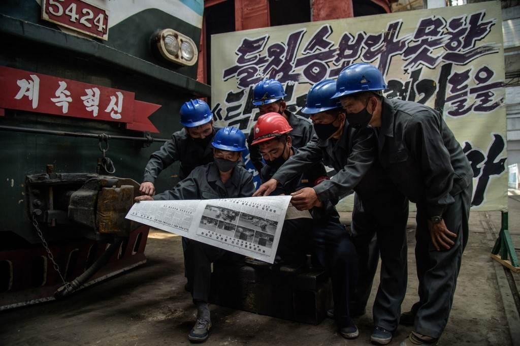 موظفون في بيونغ يانغ يقرأون نسخة من صحيفة