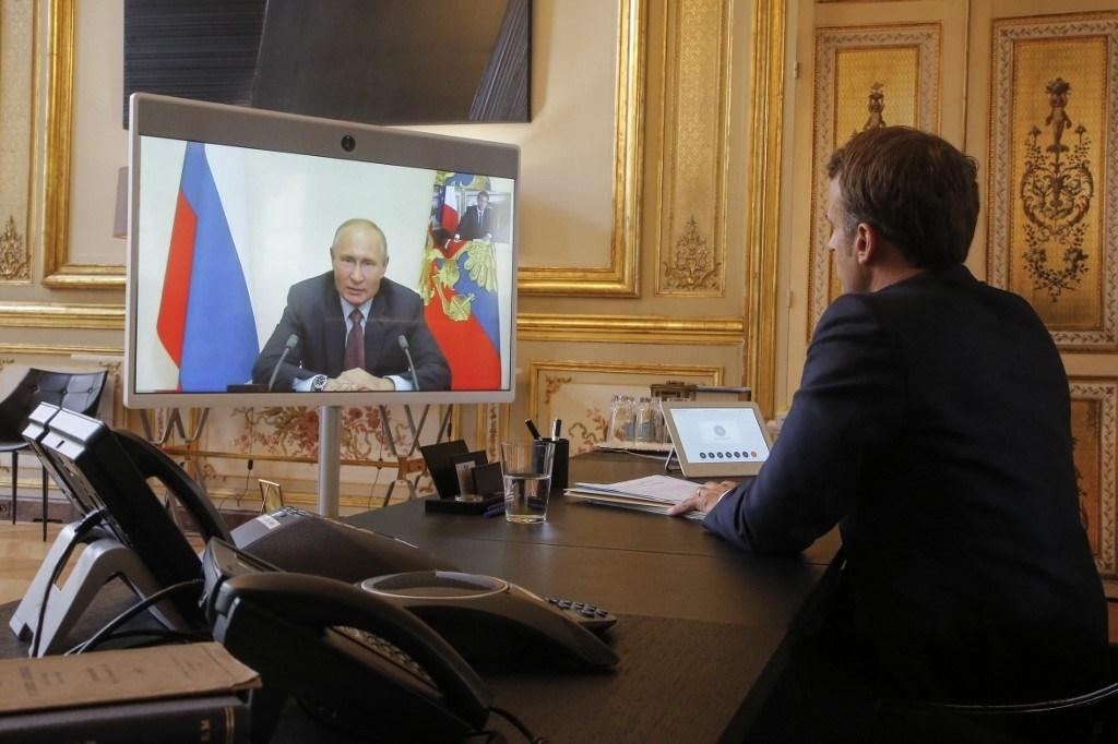 الرئيس الروسي فلاديمير بوتين ونظيره الفرنسي إيمانويل ماكرون خلال اجتماعهما الافتراضي اليوم الجمعة (أ.ف.ب)