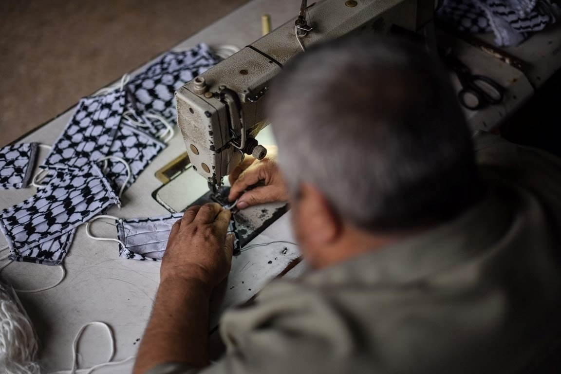 الحرفي أبو علاء غبن قام بتنفيذ مئات من الكمامات من الكوفية الفلسطينية في غزة (تصوير عبد الرحمن زقوت).