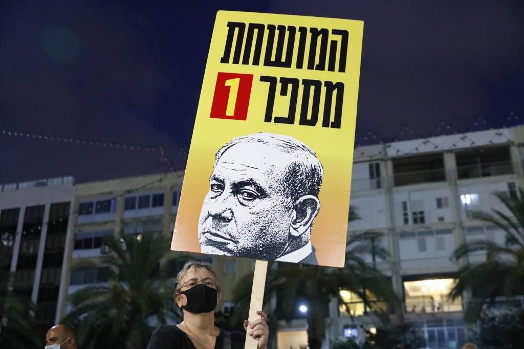 متظاهر يرفع لافتة خلال مظاهرة ضدّ سياسات نتنياهو (أ ف ب).