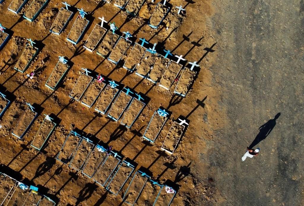 رجل يسير بجانب إحدى مقابر وفيات كورونا في مدينة ماناوس البرازيليّة يوم 21 حزيران/يونيو الماضي (أ.ف.ب)