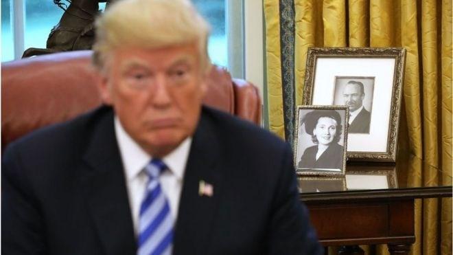 صور والد ووالدة ترامب خلف مكتبه في البيت الأبيض (Getty Images)